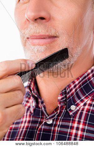 Closeup Photo Of An Aged Man Combing His Beard