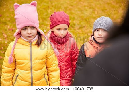 childhood, leisure, friendship and people concept - group of sad kids being blamed for misbehavior in autumn park