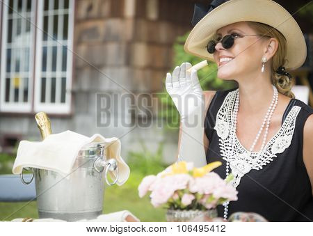 Attractive Twenties Dressed Woman Eating and Drinking Champagne At Outdoor Party.