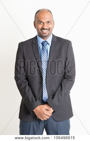 Friendly Indian businessman in formal suit looking at camera, standing on plain background.