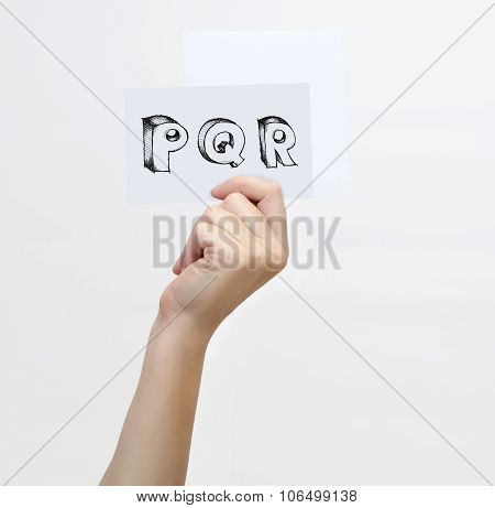 Hand Holding A Piece Of Paper With Sketchy Capital Letters  P Q R, Isolated On White.