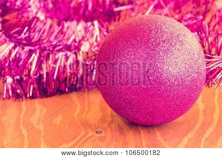 Purple Bauble And Tinsel On Wooden Background