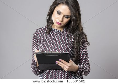 Confident Businesswoman. Confident Young Businesswoman Writing Something In Clipboard While Standing