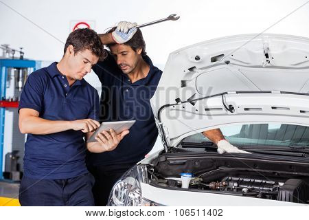 Male technicians using digital tablet by car with open hood at auto repair shop