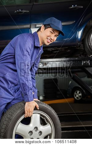 Portrait of smiling male mechanic carrying car tire at auto repair shop