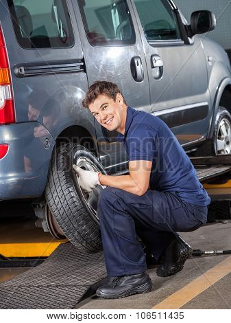 Portrait of smiling mechanic changing car tire at auto repair shop