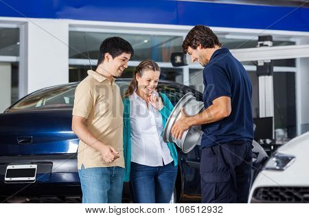 Happy technician and couple looking at metallic alloy in garage