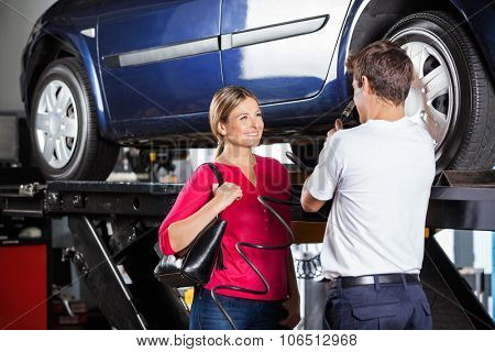 Mechanic discussing with female customer while filling car tire at garage