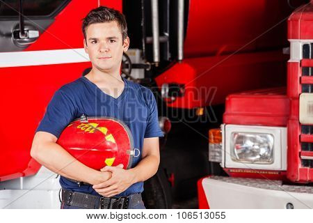 Portrait of confident male firefighter holding red helmet against firetrucks at station