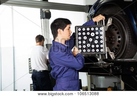 Side view of male mechanic adjusting aligner on car wheel with colleague working in background at garage