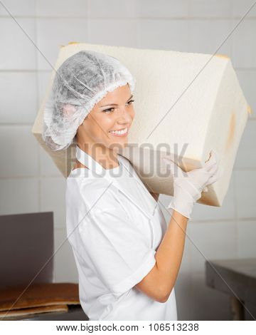 Confident female baker smiling while carrying big bread loaf in bakery