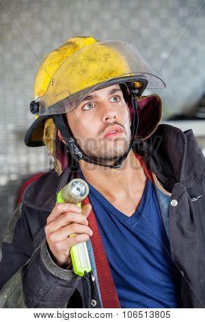 Young male firefighter looking away while holding torch at fire station
