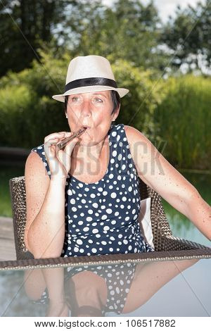 Attractive Woman Siiting By The Pool And Smoking E-cigarette