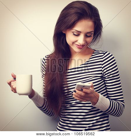 Cute Smiling Casual Woman Texting Sms On Mobile Phone And Drinking Coffee