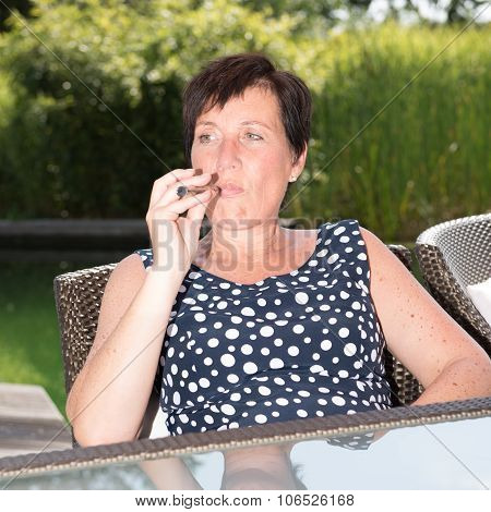 Attractive Woman Is Smoking E-cigarette In Garden