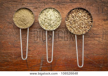 hemp seeds, hearts and protein powder in metal measuring scoops against grunge wood