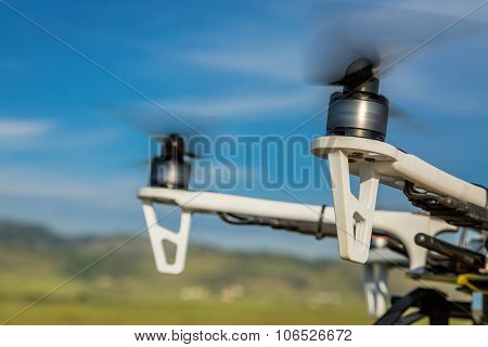 blurred spinning propellers of a hexacopter drone flying over rolling  prairie