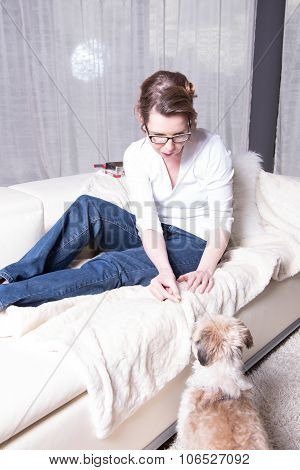 Attractive Woman On Couch Feeding Her Dog