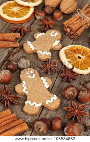 Holiday baking ingredients and gingerbread men on rustic wood