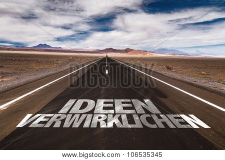 Realize Ideas (in German) written on desert road