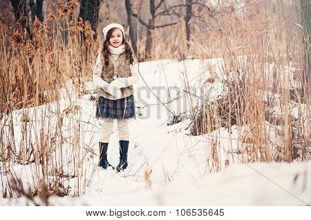 adorable dreamy kid girl on the walk in winter forest