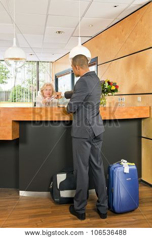 Business class passenger, with carry on luggage and priority airport labels checking in at a hotel, handing over his passport to the senior receptionist behind the counter