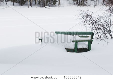 Bench Windswept Snow On The Shore Of A Frozen River In The Winter.