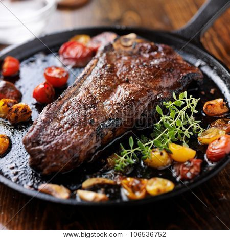 new york strip steak on iron skillet with heirloom tomatoes