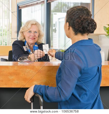 File name:     Receptionist helping a guest at a hotel, handing out the electronic key card for their room