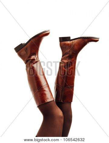 woman legs wearing brown leather high boots upside down, isolated on white