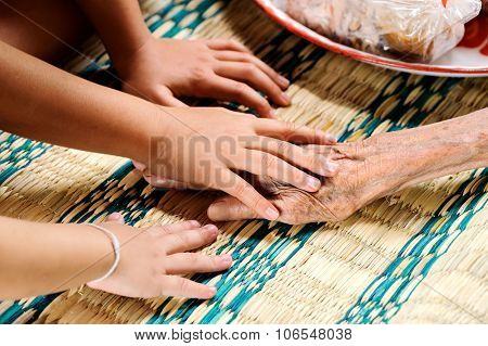 Young Hand Touches And Holds An Old Woman Hands