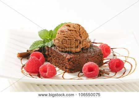 close up of brownie cake with scoop of chocolate ice cream and raspberries on white plate and place mat