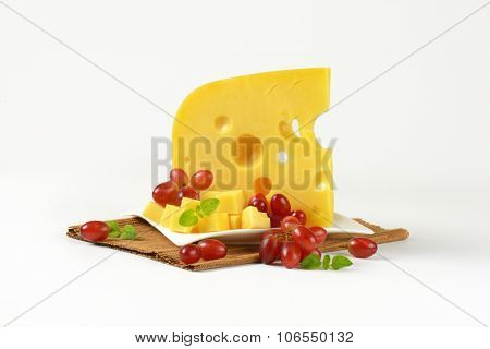 plate of fresh cheese and red grapes on brown place mat