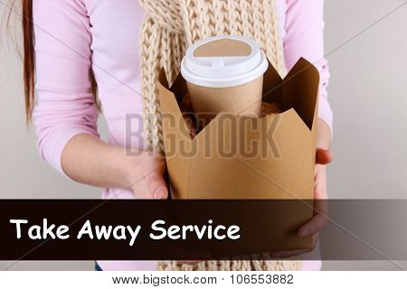 Woman holding paper bag with coffee and cookies on grey background