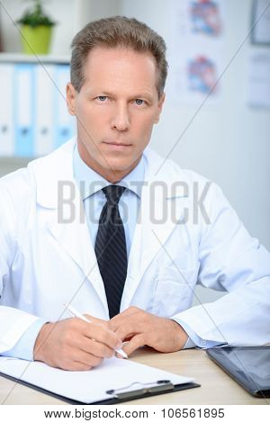 Professional doctor sitting at the table