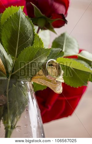 Closeup Of Engagement Ring Hanging From A Leaf Of Red Blooming Rose