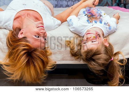 Woman And Her Daughter Lying On The Bed.