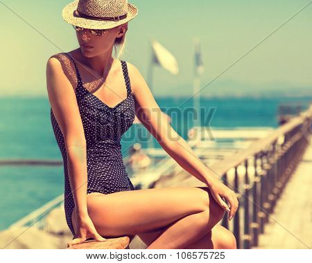 young woman in bikini swimsuit and sun hat .  	 Girl on a European beach in a bathing suit, vintage