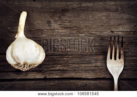 Garlic And Fork On Old Cracked Board