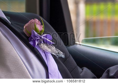 Groom's Boutonniere with a pink rose inside a car by a window going to the wedding