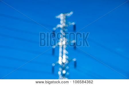 Blurry High Voltage Post Or Power Transmission Line Tower And Blue Sky