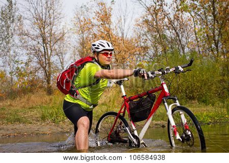 Young athlete crossing rocky terrain with bicycle in his hands.