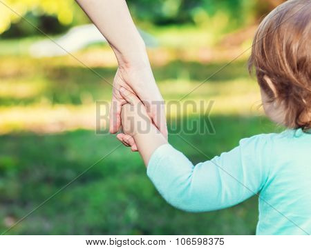 Toddler Girl Holding Hands With Her Mother