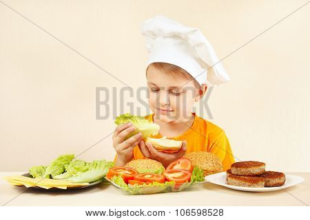 Little funny chef puts lettuce on sandwich