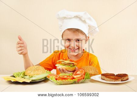 Young funny boy in chefs hat shows how to cook hamburger