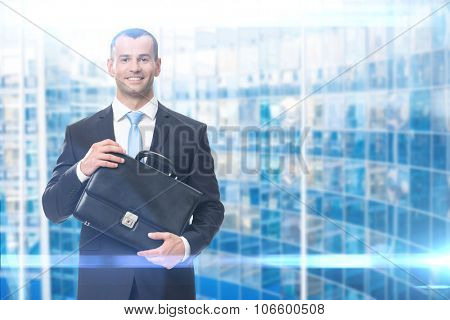 Business portrait of man keeping black leather suitcase, blue background
