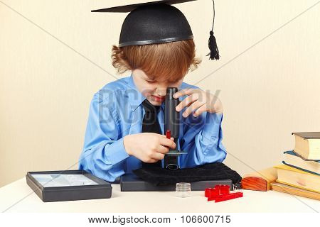 Little smart boy in academic hat looking through microscope at his desk