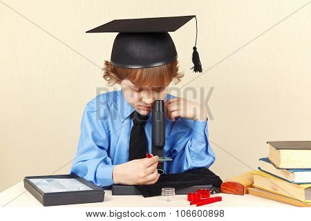 Little professor in academic hat looking through microscope at his desk