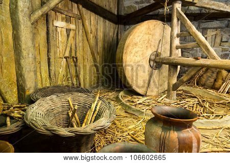 Close up of wooden equipment, instruments and straw in the shed. Millstone interior