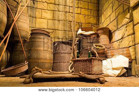 Old lit lumber-room with wooden baskets, barrels and ropes